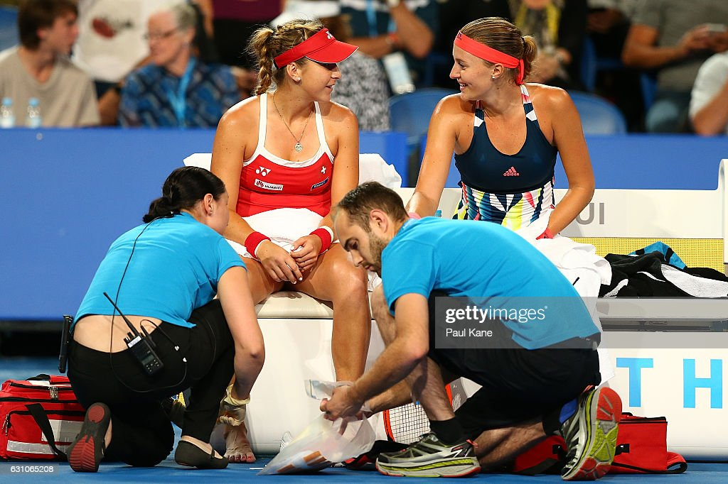Belinda Bencic of Switzerland and Kristina Mladenovic of France share a moment on the Swiss bench as trainers attend to an injured toe in the women's singles match during day six of the 2017 Hopman Cup at Perth Arena on January 6, 2017 in Perth, Australia.