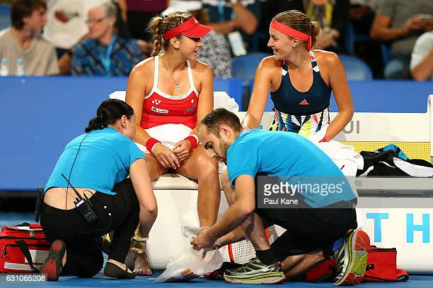Belinda Bencic of Switzerland and Kristina Mladenovic of France share a moment on the Swiss bench as trainers attend to an injured toe in the women's...