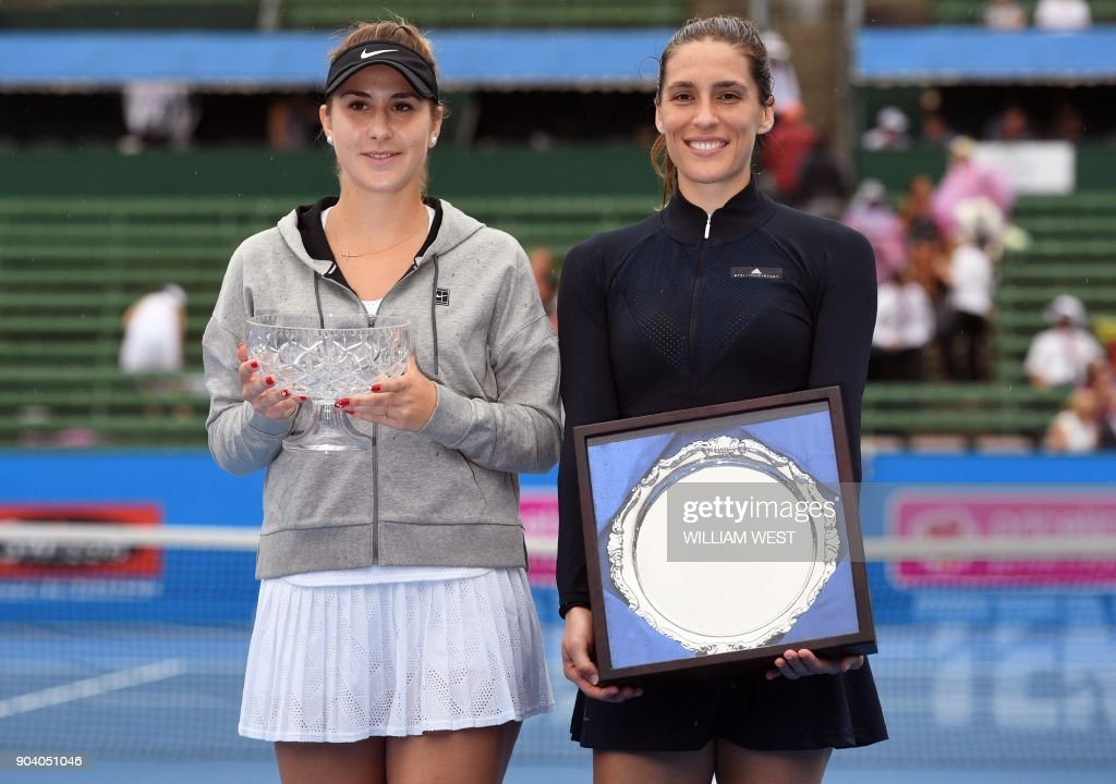 Belinda Bencic of Switzerland (L) holds the trophy with runner-up Andrea Petkovic of Germany (R) after the women's singles final match of the Kooyong Classic tennis tournament in Melbourne on January 12, 2018. / AFP PHOTO / William WEST / IMAGE