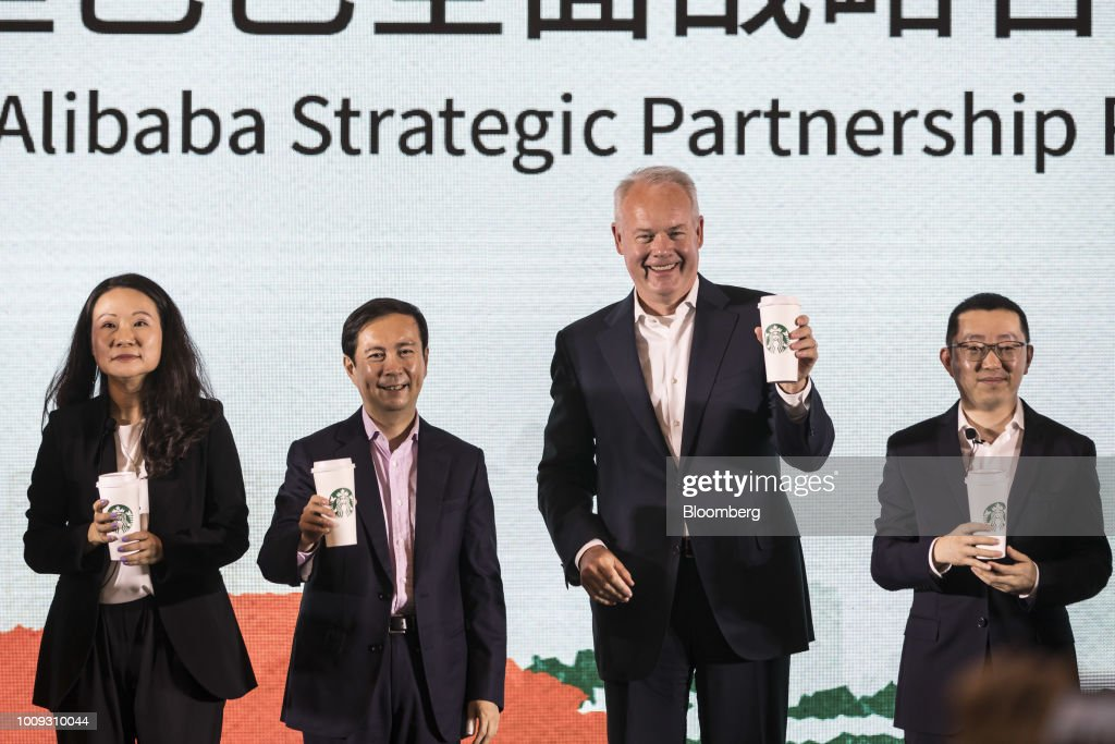 Belinda Wong, chief executive officer of China at Starbucks Corp., from left, Daniel Zhang, chief executive officer of Alibaba Group Holding Ltd., Kevin Johnson, chief executive officer of Starbucks Corp., and Wang Lei, chief executive officer of Alibaba's food delivery platform Ele.me, hold Starbucks cups during a news conference in Shanghai, China, on Thursday, Aug. 2, 2018. Starbucks is joining forces with Alibaba to begin delivering its drinks and baked goods in China, rolling out an effort to stave off competitors and turn around sales in the country. Photographer: Qilai Shen/Bloomberg via Getty Images