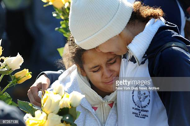 Belkis Lora who lost her brother 44yearold Jose Lora cries with Alexandra Baez during a memorial service this morning on the fourth anniversary of...