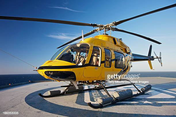a bell 407 utility helicopter on the helipad of an oil rig. - helicopter photos stock pictures, royalty-free photos & images