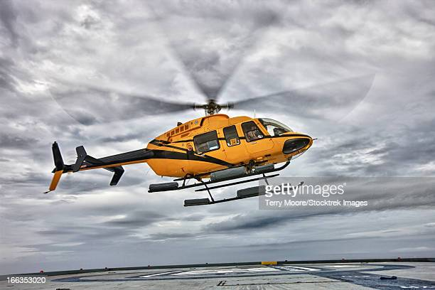 a bell 407 utility helicopter prepares to land on the helipad of an oil rig. - helicopter photos stock pictures, royalty-free photos & images
