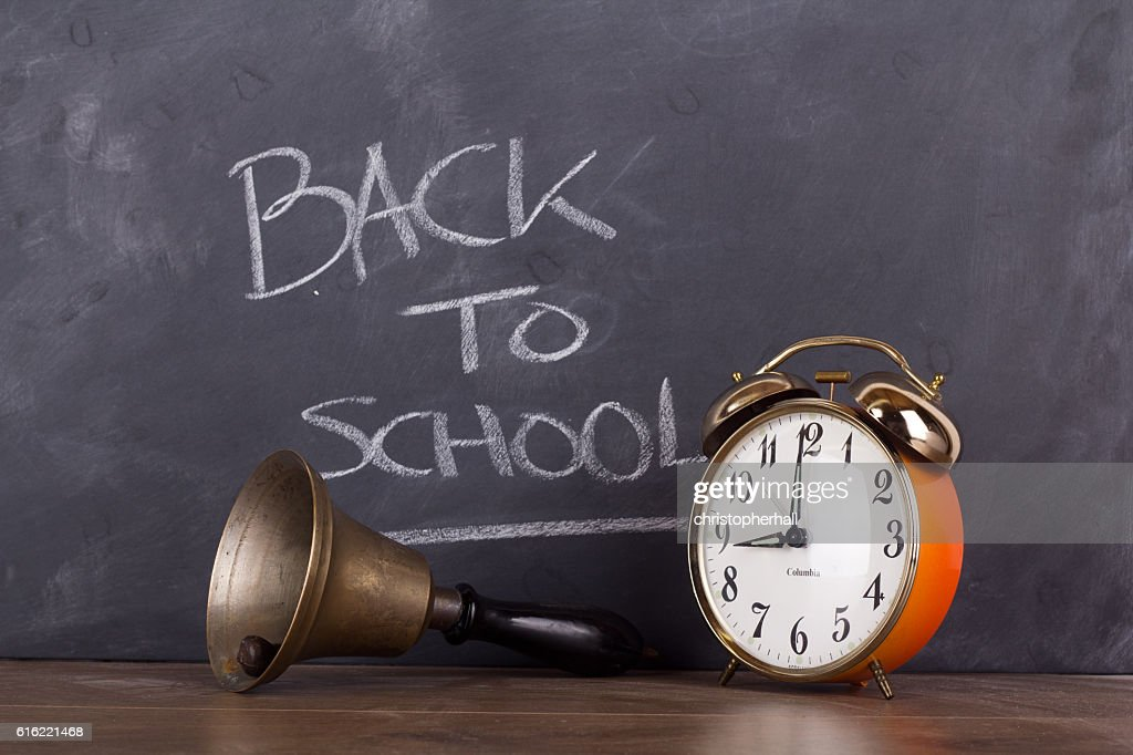 Bell and alarm clock against a blackboard : Stockfoto