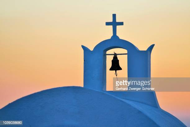 bell and cross of a church in the last evening light with an orange-red sky, oia, ia, santorin, cyclades, greece - last stock pictures, royalty-free photos & images