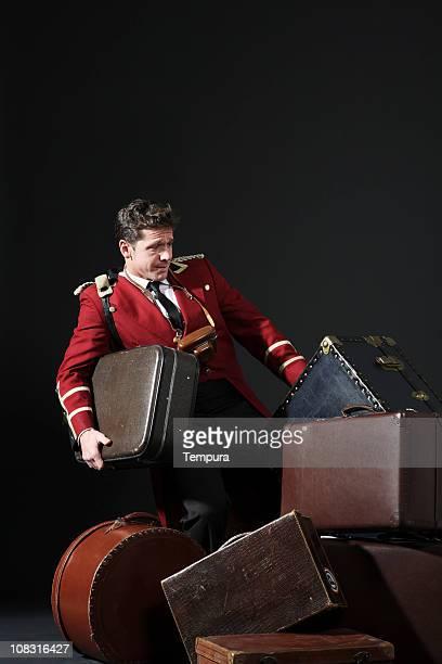 Bell boy pulling a heavy trunk in hotel.