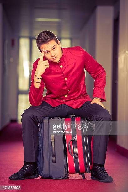 Bell boy sitting on suitcase