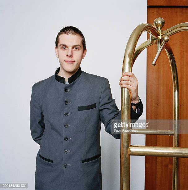 Bell boy standing next to luggage cart in hotel, portrait