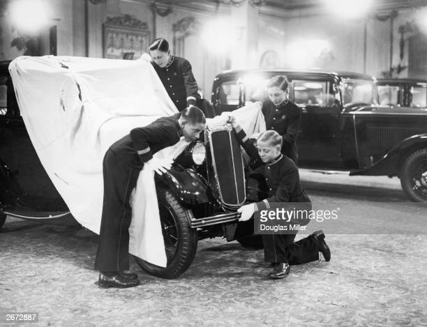 Bell boys take a peep at one of Lord Nuffield's new Baby Morris motor cars on show at the Grosvenor House Hotel in London.