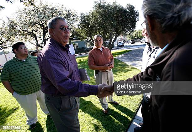 Bell City Councilman Lorenzo Velez center left shakes hands with Bell citizen Eddie Perez right as he chats with Perez and Jose Vasquez center and...