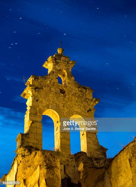 Bell tower of a ruined, abandoned, one night with sky of stars in movement