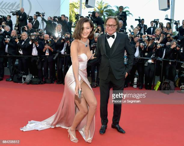 Bella Hadid smiles as she picks up a camera battery which a photographer dropped on the red carpet before giving it back as she attends the 'Ismael's...