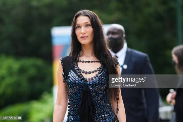 Bella Hadid wears a black pearls necklace from Louis Vuitton, a black sequins / glitter shiny sleeveless short dress with knot on the chest and tulle...
