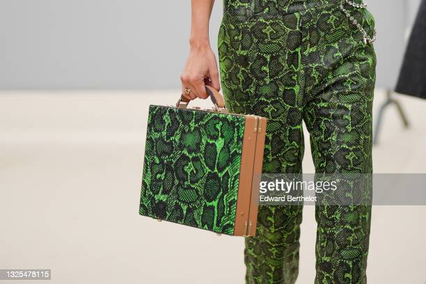 Bella Hadid wears green leather snake print pattern flared pants, a rigid square briefcase bag with green snake print pattern, outside Dior, during...