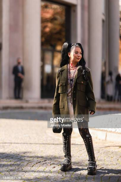 Bella Poarch wearing a olive jacket, black pants and black boots outside Miu Miu Show on October 05, 2021 in Paris, France.