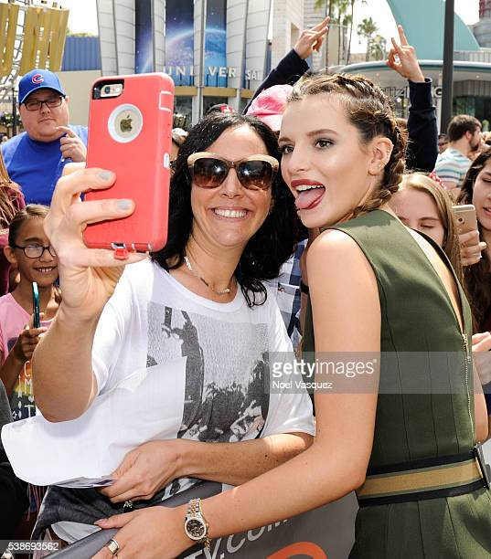 """Bella Thorne takes a selfie with fans at """"Extra"""" at Universal Studios Hollywood on June 7, 2016 in Universal City, California."""