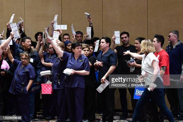 Bellagio hotel workers hold up their balllots during the Nevada caucuses to nominate a Democratic presidential candidate at the caucus polling...