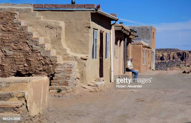 Bellamino a Native American artist sits in front of an adobe home at Sky City one of three Native American villages which make up Acoma Pueblo west...