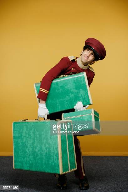 Bellboy carrying heavy luggage