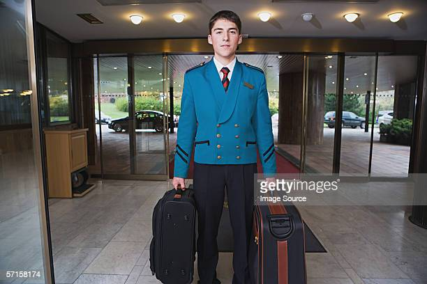 Bellboy carrying suitcases