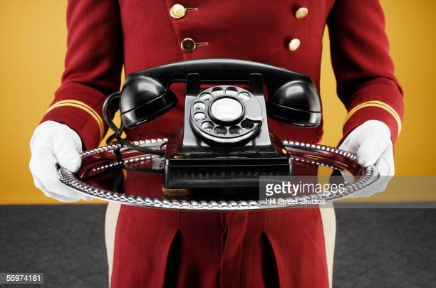 Bellboy delivering telephone on silver platter