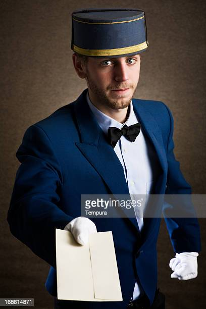 bellboy holding an envelope as copy space - doorman stock photos and pictures