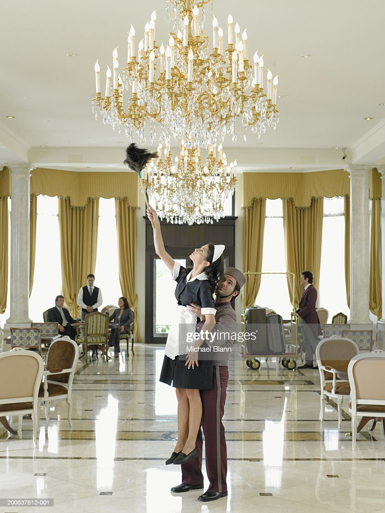 Hotel Foyer Chandelier : Bellboy holding up maid dusting chandelier in hotel foyer