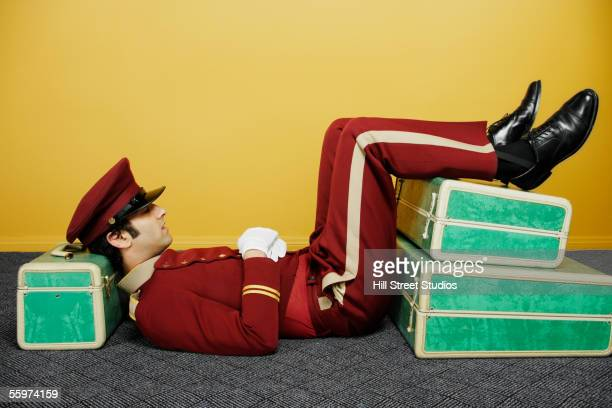 Bellboy reclining on suitcases