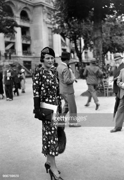 Belle création estivale portée par une jeune femme à l'hippodrome d'Auteuil à Paris France en juin 1933