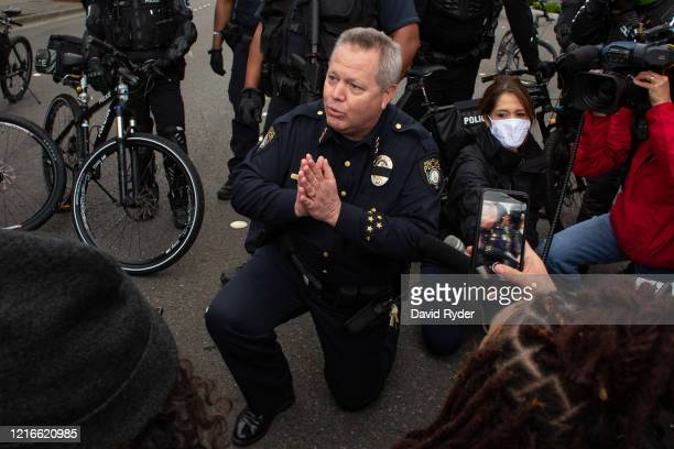 Bellevue Police Chief Steve Mylett kneels next to demonstrators while talking with them during a gathering to protest the recent death of George...