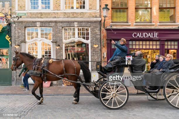 ブルージュのマーケットスクエアのベルフリーと市庁舎、ブルージュの中心部の人気ベルギーの目的地ブルージュツアーで観光客を待っている茶色の馬とフィアカー - 四輪馬車 ストックフォトと画像