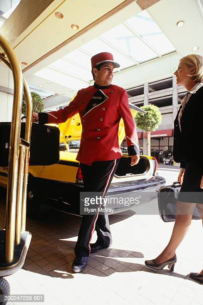 Bellhop carrying businesswoman's luggage
