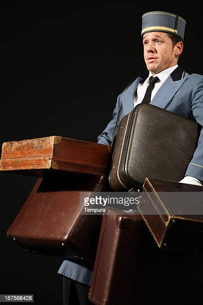 bellhop carrying many suitcases