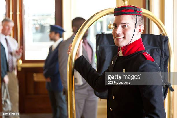 Bellhop holding luggage cart while waiting for hotel guests