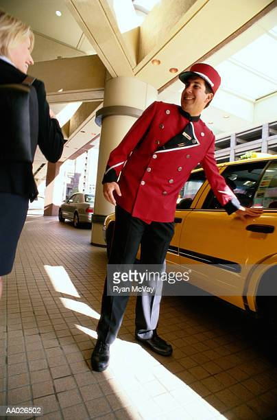 bellhop opening a taxi car door for businesswoman - doorman stock photos and pictures