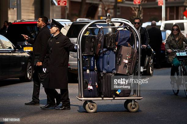 A bellhop pulls a cat with luggage outside the Mandarin Oriental hotel in New York US on Friday April 5 2013 Hotel developers are shunning luxury...