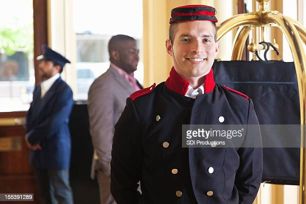 Bellhop standing in hotel lobby with guest's luggage on cart
