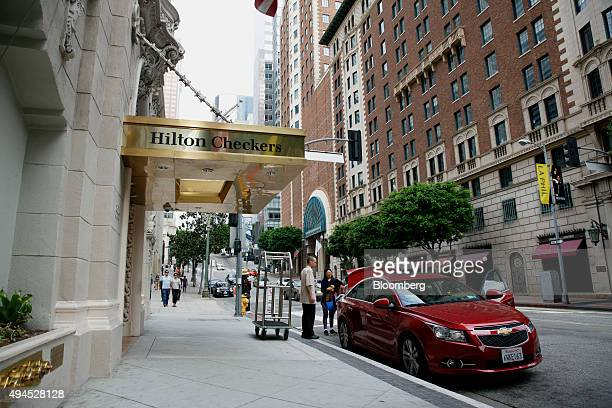 A bellhop unloads bags from a car outside of the Hilton Checkers hotel in downtown Los Angeles California US on Sunday Oct 25 2015 Hilton Worldwide...