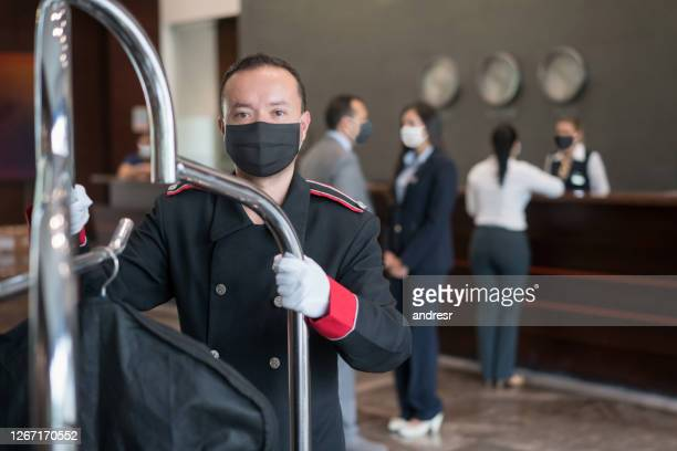 bellhop working at a hotel wearing a facemask - biosecurity stock pictures, royalty-free photos & images