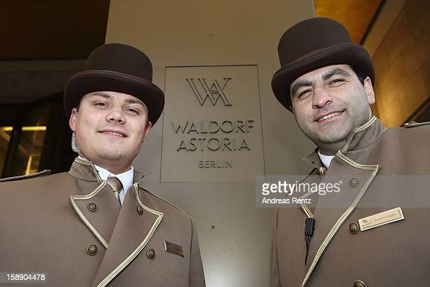 Bellhops stand near the company emblem during the opening of Germany's first Waldorf Astoria hotel on January 3 2013 in Berlin Germany The luxury...