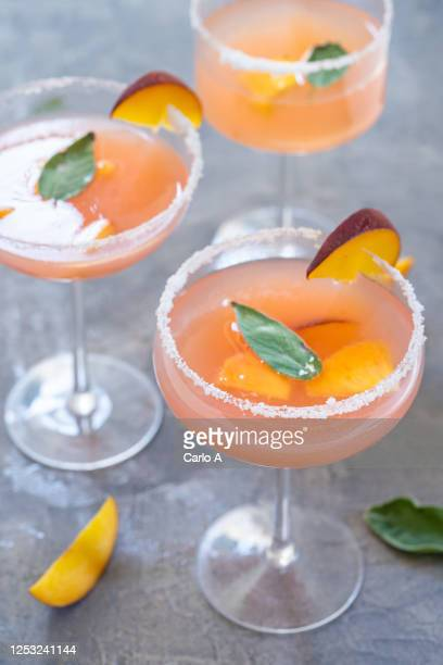 bellini cocktails with peach fruit and sage leaves. - cocktail stock pictures, royalty-free photos & images