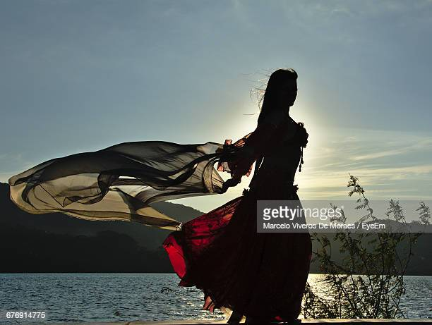 belly dancer with wind blown scarf at lakeshore - belly dancing stock photos and pictures