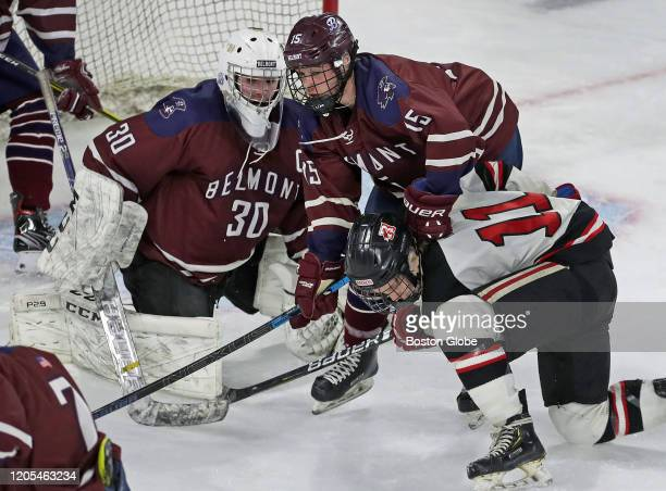 Belmont High School's Nolan Duffy clamps down on Reading's Sean Golden in front of Belmont goalie Nico Carere in first period action Reading High...