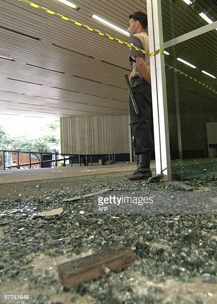 Un policia monta guardia junto a la puerta de la Compania de Energia del Estado de Minas Gerais con sus vidrios rotos por miembros del Movimiento de...