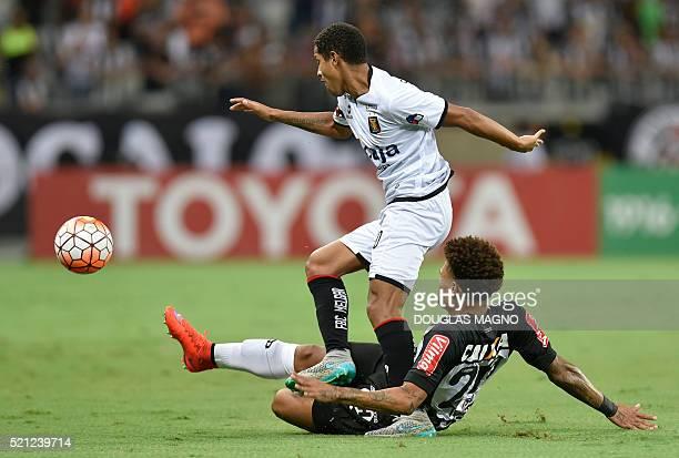 Brazilian Atletico Mineiro player Junior Urso vies for the ball with Peruvian Melgar player Alexander Sanchez during their 2016 Libertadores Cup...