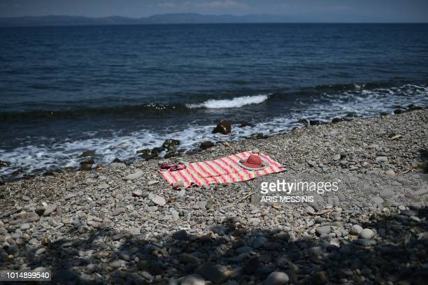 Belongings of a bather are seen on a beach near the village of Skala Sykamineas on the Greek island of Lesbos on August 3 2018