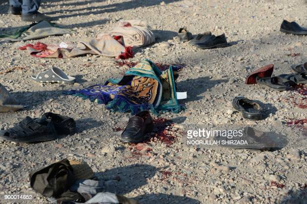 TOPSHOT Belongings of blast victims lay in the ground at the scene of a suicide attack that targeted a funeral ceremony in Jalalabad on December 31...