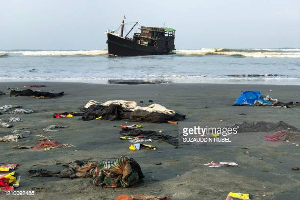 Belongings of Rohingya refugees lay on the shore as their carrier boat remains anchored nearby in Teknaf on 16 April 2020. - Thirty-two Rohingya died...