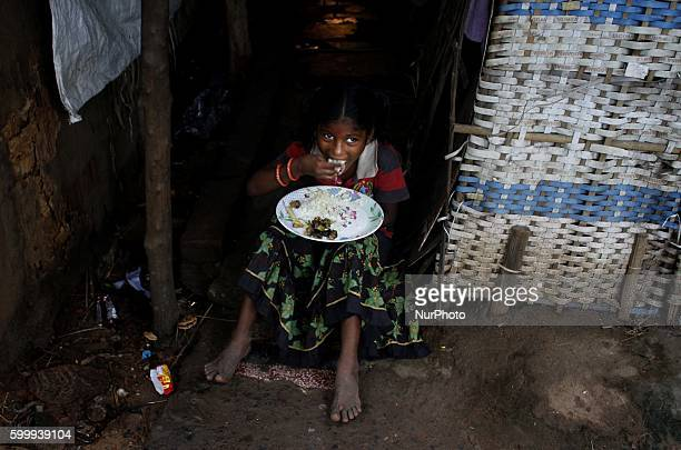 A below poverty line family girl eats food as she sits outside of her parents living makeshift at a slum in the eastern Indian city Bhubaneswa on 7...