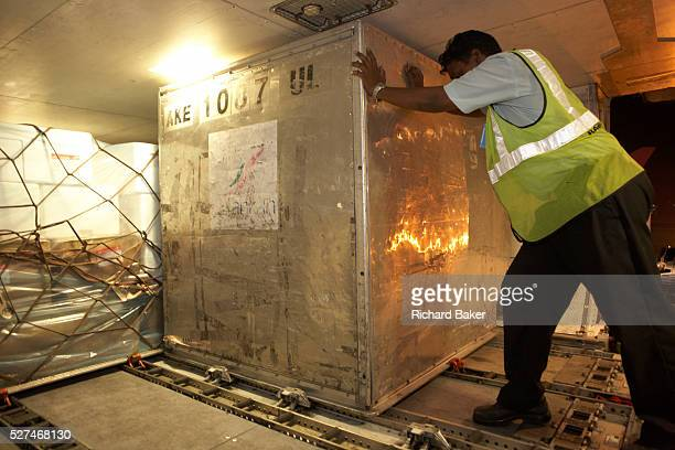 Below the flooring of economy class a cargo handler manhandles a container of air freight into position in the hold of a Sri Lankan Airlines Airbus...